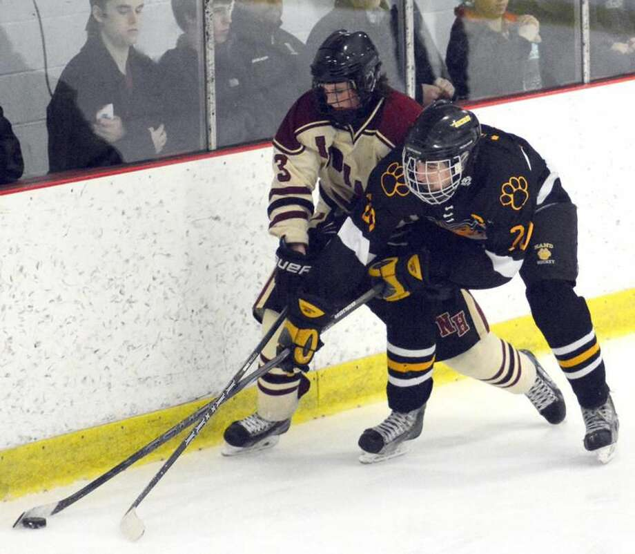 Photo by Dave Phillips North Haven's Tyler Luedee battles Hand's Dan Healey for the puck in the CIAC Division II quarterfinals.