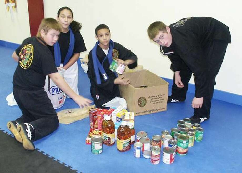 Submitted Photo Students from the Academy of Kempo Martial Arts in Hamden separating the food collected in November for Saint Ann's Soup Kitchen and the Keefe Center's Food Bank. The Academy kicked off their annual food drive in September and has donated more than 35 bags of food to date. The Academy is offering students a free semi-private lesson for any five or more non-perishable items they donate and offering two weeks of free lessons to non-students. Pictured, left to right, are Colt Pimer, Maya Caicedo, Antonio Rodriguez and Chris Pimer.