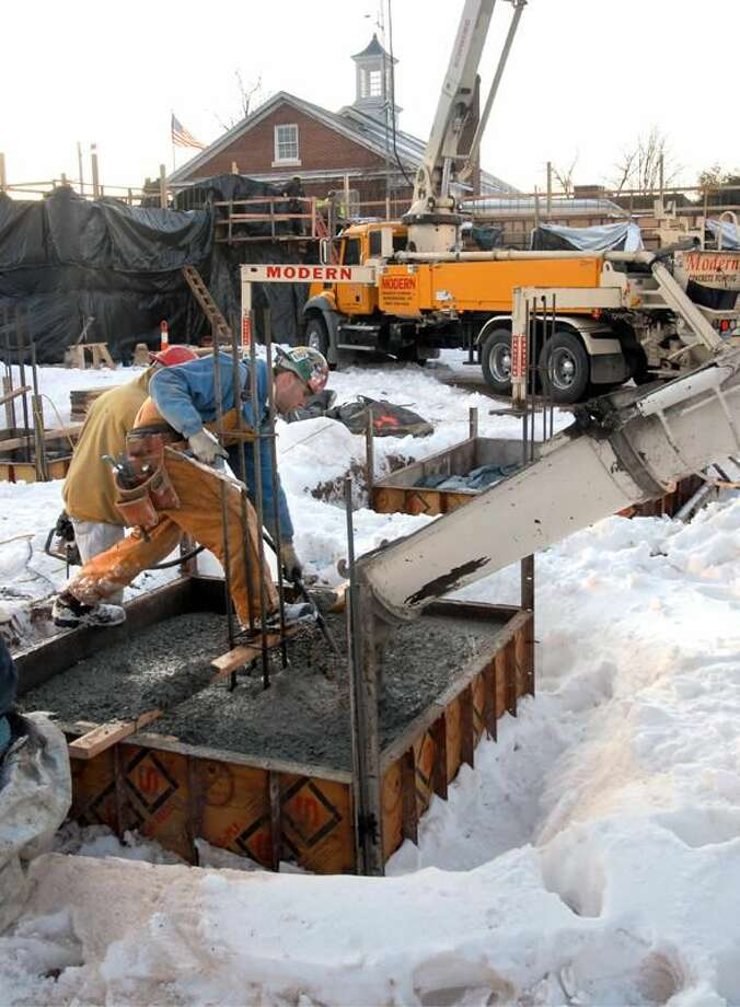 Photo by Mara Lavitt/Register Construction continues near Hamden's Memorial Town Hall. Here, Waterbury Masonry & Foundation workers pour column footings for the new police headquarters.
