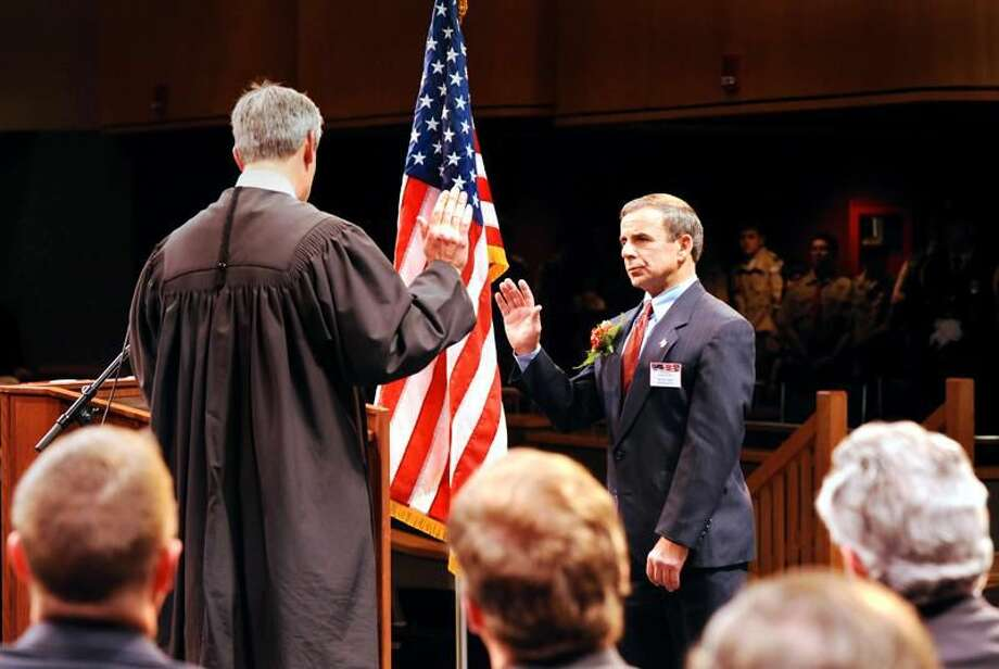 Photo by Peter Hvizdak/Register Michael J. Freda, right, is sworn in as the North Haven First Selectman by Superior Court Judge Brian T. Fischer during the town's inauguration ceremony for government officials Monday night at North Haven High School.