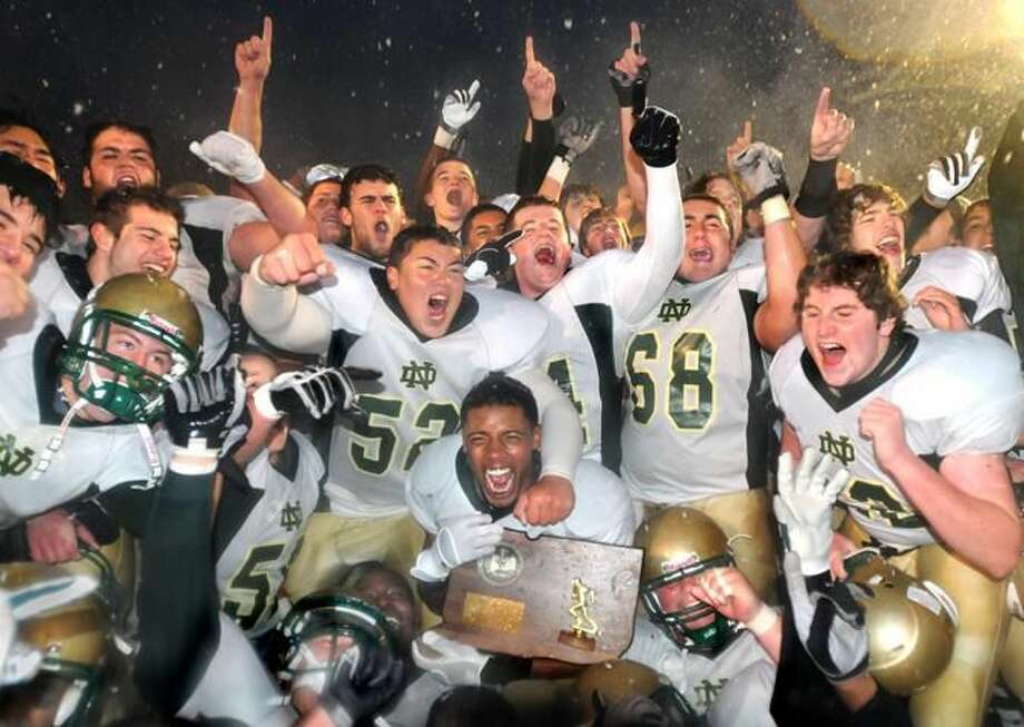 The Notre Dame-West Haven football team celebrates its Class L championship after defeating Pomperaug 28-21 at Finn Stadium in Shelton. (Photo by Melanie Stengel/ New Haven Register)