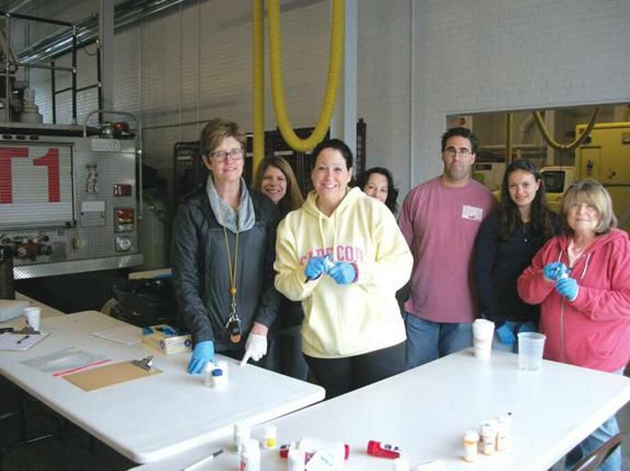 Photos by Lynn Fredricksen Several town employees were among numerous volunteers who participated in the town's prescription drug take-back collection held at Fire Headquarters on Saturday. Pictured left to right are Nancy Leddy and Carla Riccio of the Community Services Department, Valerie Goodkin, executive assistant to First Selectman Michael Freda, and volunteers Kim DiMeola, Angelo Annunziato, Maia Annunziato and Gina Cretella. Missing from the photo is Ed Swinkoski, Finance Director for the town, who manned the booth for most of the day.