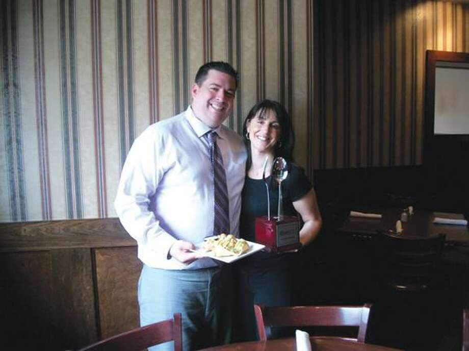 Photo by Lynn Fredricksen Eli's on Whitney is the place to go for Philly cheesesteak eggrolls. Here, general manager Kevin Fitzsimmons and his wife, Lisa Votto, show off a plate of the award-winning noshes along with the prized trophy.