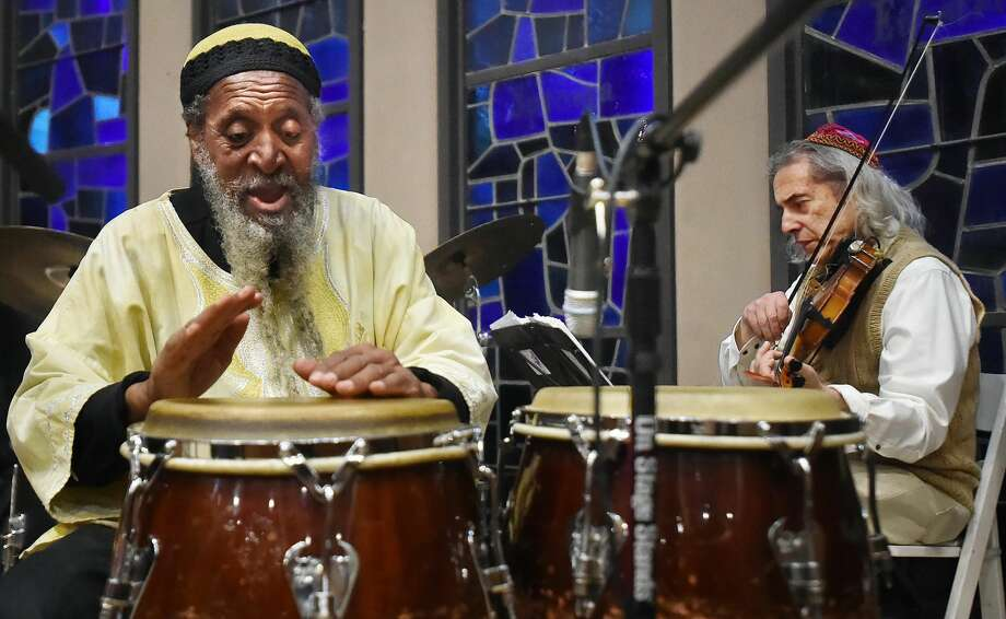 Alvin Abu Carter plays the congos and violinist Stacy Phillips, members of the Afro-Semitic Experience perform at the annual interfaith service in tribute to Martin Luther King Jr. at Congregation Mishkan Israel in Hamden on Friday.