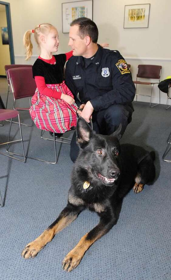 """Photo by Peter Casolino Hamden Police Officer Mike Nawrocki shares a moment with his daughter, Julia (5), moments after his dog """"Hank"""" was sworn in as the newest member of the department at Town Hall."""