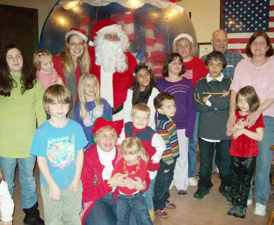 Submitted Photo Pictured are Lodge members, their children and grand-children attending the party. Shown at Santa's right to accept the Elks donation is Youth Continuum Director of Development Michelle Doheney.