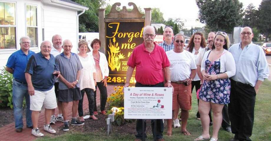 Submitted Photo Above, Proudly displaying a 'Wine & Roses' sign, John Henry Graef, Jr. was one of several wine makers honored by the North Haven Rotary Club at the annual picnic for competing winemakers. Below, winemakers and other guests enjoy teh annual picnic.