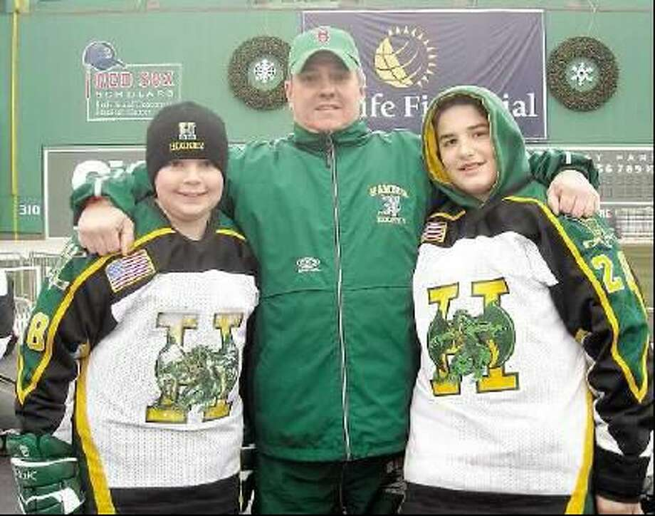 A.J. Mills, right, lost his father James in early November, but hockey and his Hamden Dragons Bantam B teammates have been a refuge for him this season. On Friday the team will attend the Winter Classic at Fenway Park after being one of five teams invited by the Bruins. Also pictured are Nick Piasecki, left, and coach Jim Wilson. (Submitted photo)