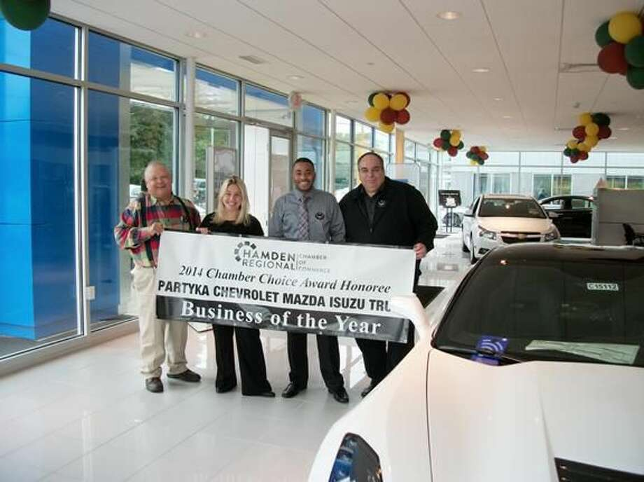 Photo by Lynn Fredricksen Lee Partyka, Amy Partyka, Andrew Quintyne and Joseph Gallagi proudly display the banner presented to them by the Hamden Regional Chamber of Commerce. The Skiff Street dealership has been named Business of the Year and will be formally recognized at the HRCC's Chamber Choice Awards ceremony Nov. 13 at Cascade in Hamden.