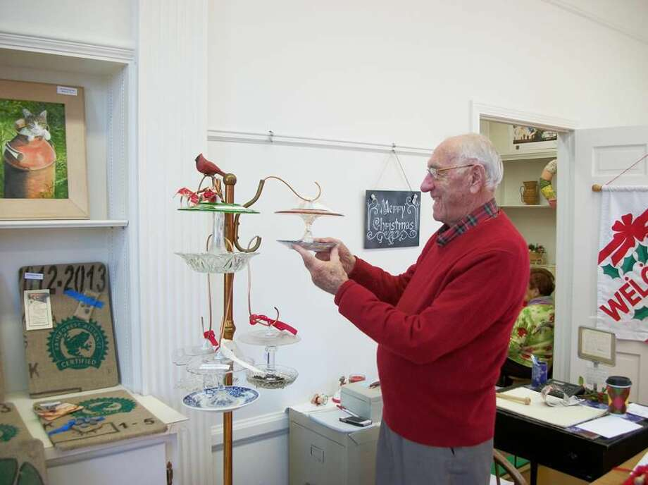 Photo by Lynn Fredricksen North Haven Art Guild President Joe Fiore admires some glass bird feeders at the Holiday Boutique presented by the Art Guild.