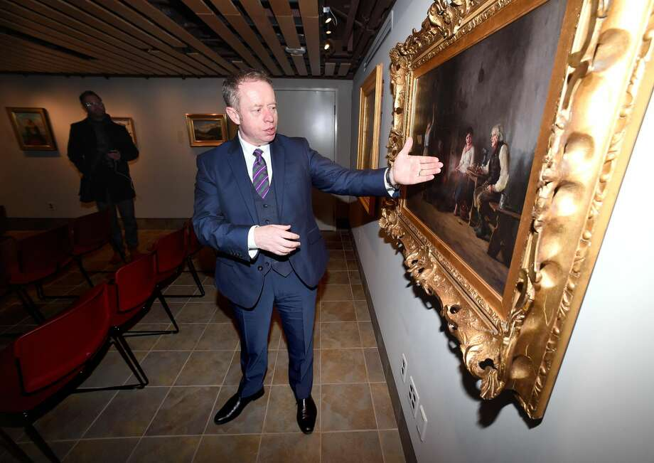Ciaran Cannon, Irish Minister of State at the Department of Foreign Affairs and Trade, views the oil painting, Mending the Nets, from 1886 by Howard Helmick during a visit to Quinnipiac University's Great Hunger Museum in Hamden on February 8, 2018.