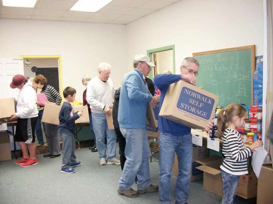 Photo by Lynn Fredricksen Dozens of volunteers lined up to pack non-perishable food donations into boxes for distribution to needy families. Ninety families received all the fixings for a complete Thanksgiving dinner from the Food Bank housed at the North Haven Congregational Church.