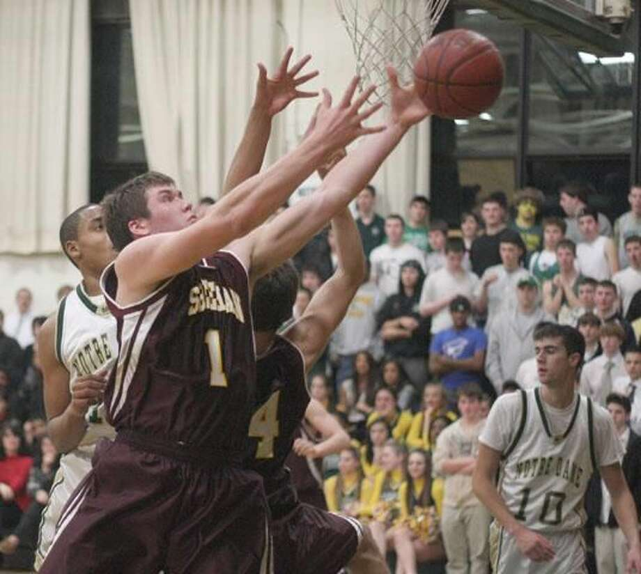 Sheehan senior Brett Biestek reaches for a rebound in an early-season game against Notre Dame-West Haven. Biestek set the school rebounding record in Friday's 59-47 win over Notre Dame. (Photo by Russ McCreven)
