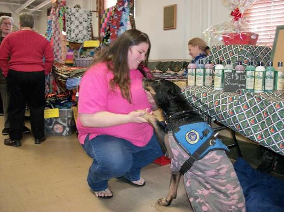 Photo by Lynn Fredricksen Therapy dog Uolie shares a special moment with Kara Staroski of Grooming Tails in Guilford. The 16-year-old beauceron often visits nursing homes and schools throughout the region.