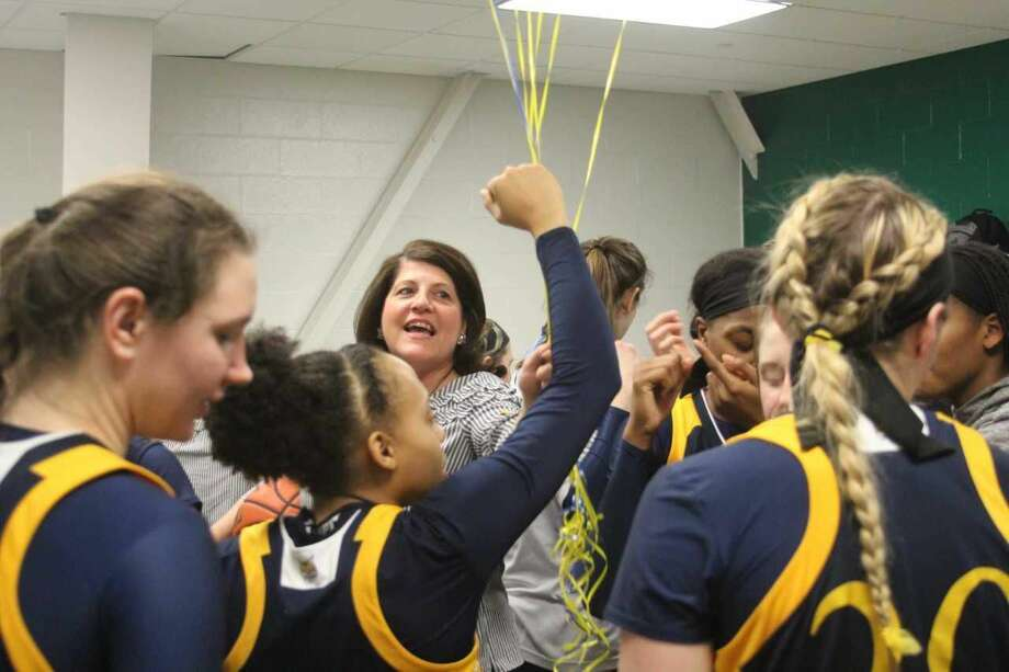 Quinnipiac women's coach Tricia Fabbri celebrates with her team after career victory 400 on Sunday, 83-72 at Siena.