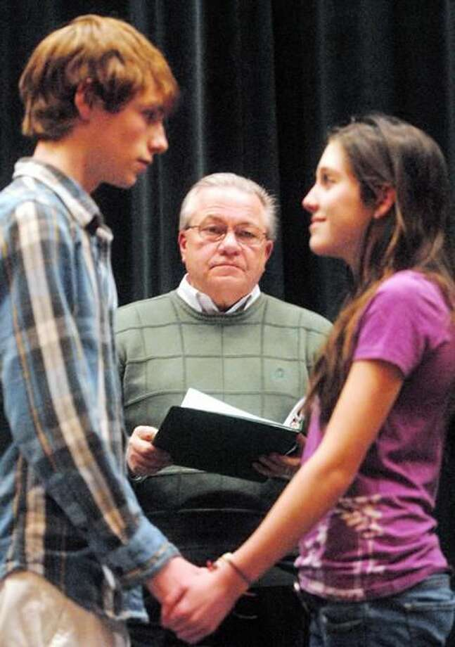 """Photos by Brad Horrigan Director Ed Handi, center, looks on as Brett Pelligrino and Gabi Carrubba go through their lines in a rehearsal for North Haven High School's production of """"The Music Man"""" Friday."""