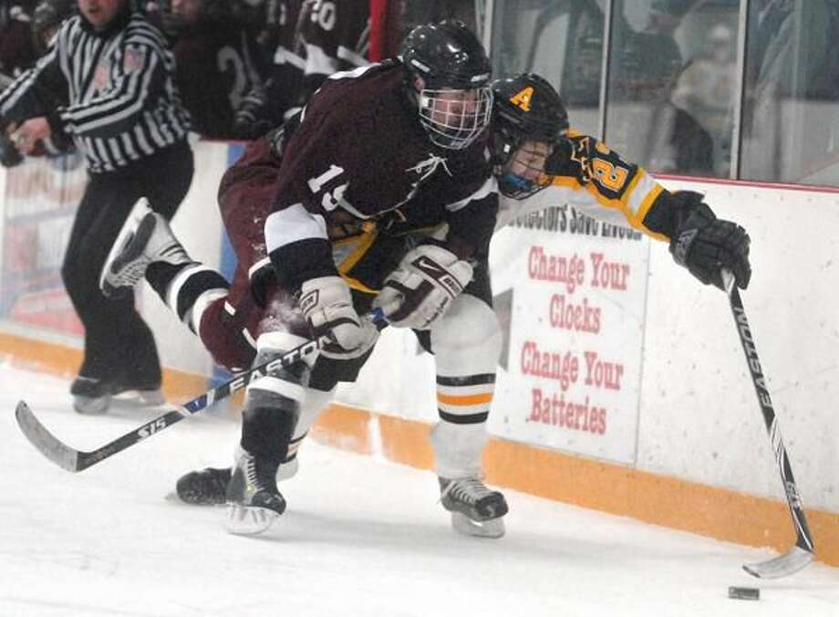 North Haven's Adam Lye tries to wrestle the puck away from Amity's Corey Shea in the Indians' 7-3 loss last week. (Photo by Brad Horrigan/ New Haven Register)