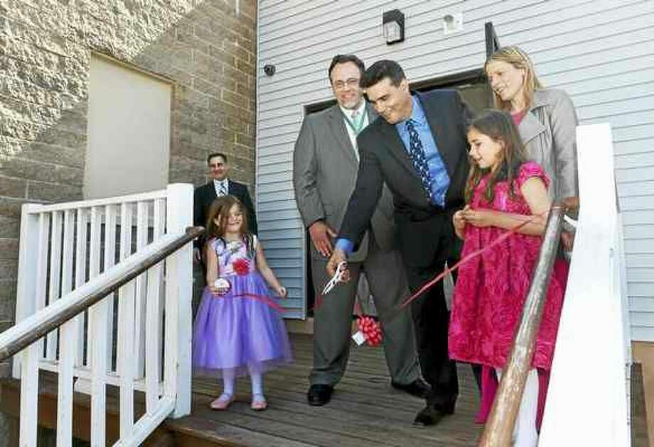 Peter Hvizdak — New Haven Register Attorney Bernie Pelligrino, far left, watches Sienna Natale, 5, Hamden Mayor Curt Leng, developer Joseph Natale, his other daughter, Miley Natale, 7, and his wife, Stacey Natale, during a ribbon-cutting ceremony that officially opened his Millstone Apartment building at 383 Putnam Ave. in Hamden.