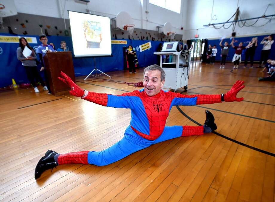 North Haven First Selectman Mike Freda dressed as Spiderman does a split for students in the gymnasium of Ridge Road Elementary School in North Haven during the Spell to Soar rally to kick off fundraising for a playground to accommodate children with disabilities.