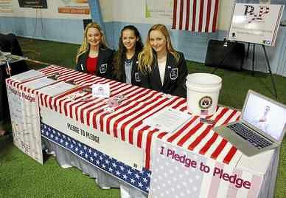 """At the Hamden Regional Chamber of Commerce's Business and Community Expo last Wednesday, Brittney Stoyer, Brittney Cifarelli and Meghan Basilici, all juniors at Hamden High School and members of DECA, promote their """"Pledge2Pledge"""" campaign, encouraging people to recite the Pledge of Allegiance. (Kate Ramunni — New Haven Register)"""