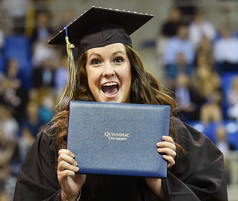 Erin K. Lapreade of Seekonk, Mass. shows her diploma to her parents after receiving a bachelor of science degree from the School of Health Sciences at the 85th commencement at Quinnipiac University at the TD Bank Sports Center in Hamden.