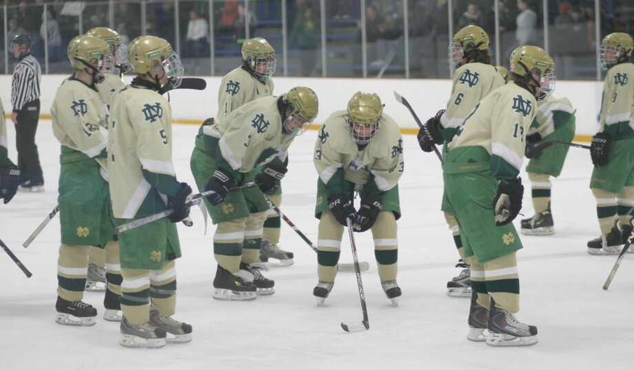 Notre Dame hockey players stand dejectedly after a Hamden goal in the Green Knights' 4-3 loss last Wednesday at the Edward L. Bennett Rink in West Haven. With the loss, Notre Dame finished with a 7-12-1 record and failed to qualify for the state tournament for the first time in 19 years. The Green Knights closed the season with eight straight losses. (Photo by Russ McCreven)