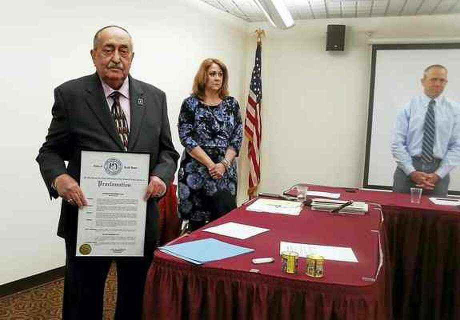 KATE RAMUNNI — NEW HAVEN REGISTER Stanley Sosensky, left, with the proclamation First Selectman Michael Freda presented to him Thursday night during the Board of Selectmen meeting.