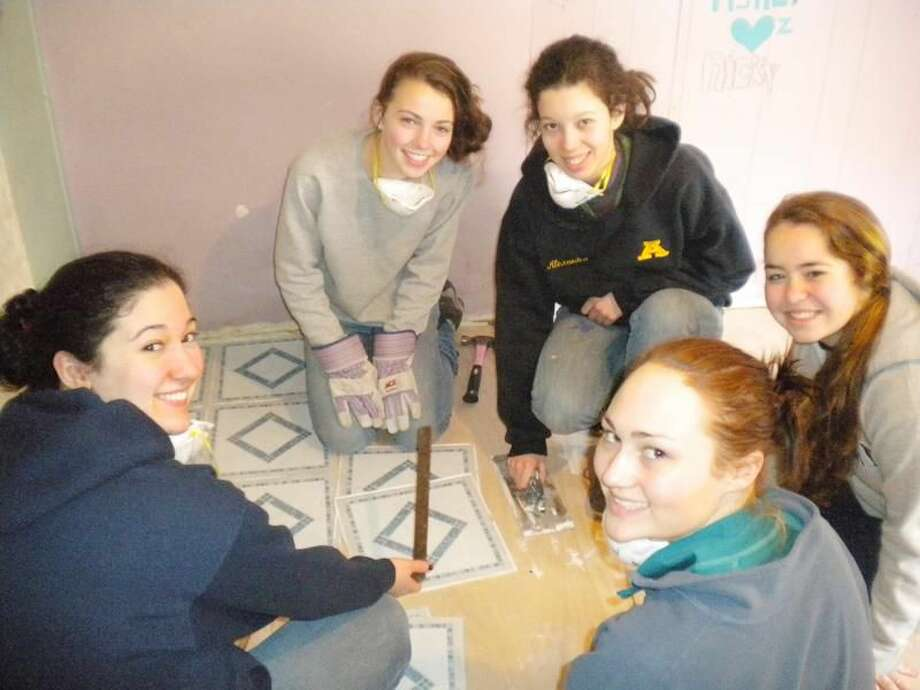 Submitted Photo Front: Caitlin Axtmayer of Wallingford, and Emma Dwyer and Liza Gillooly, both of North Haven; Back: Kiki Bowman of Cheshire and Alex Buda of Woodbridge — were among 30 students and 12 chaperones from Sacred Heart Academy who traveled to Brenton, W.V., over winter break. This group is shown replacing floor tiles in one of the trailers they worked on.
