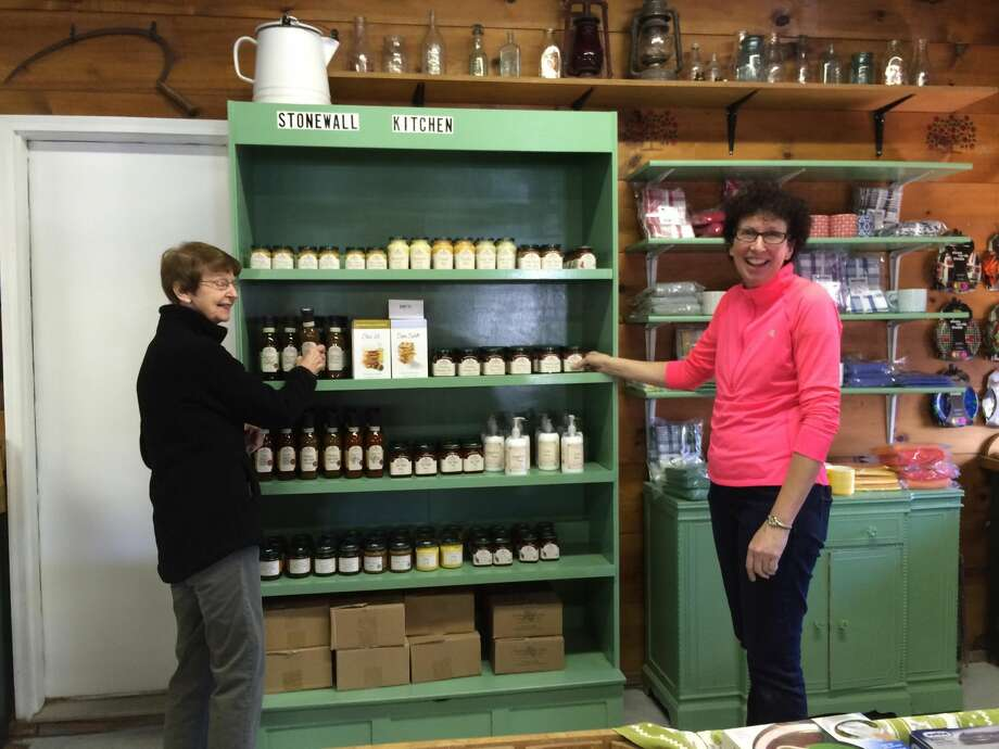Photo by Lynn Fredricksen Anne and Liz Hindinger put the finishing touches on one of the new displays at their family-owned farm market over the weekend in anticipation of opening day on Wednesday, May 4.
