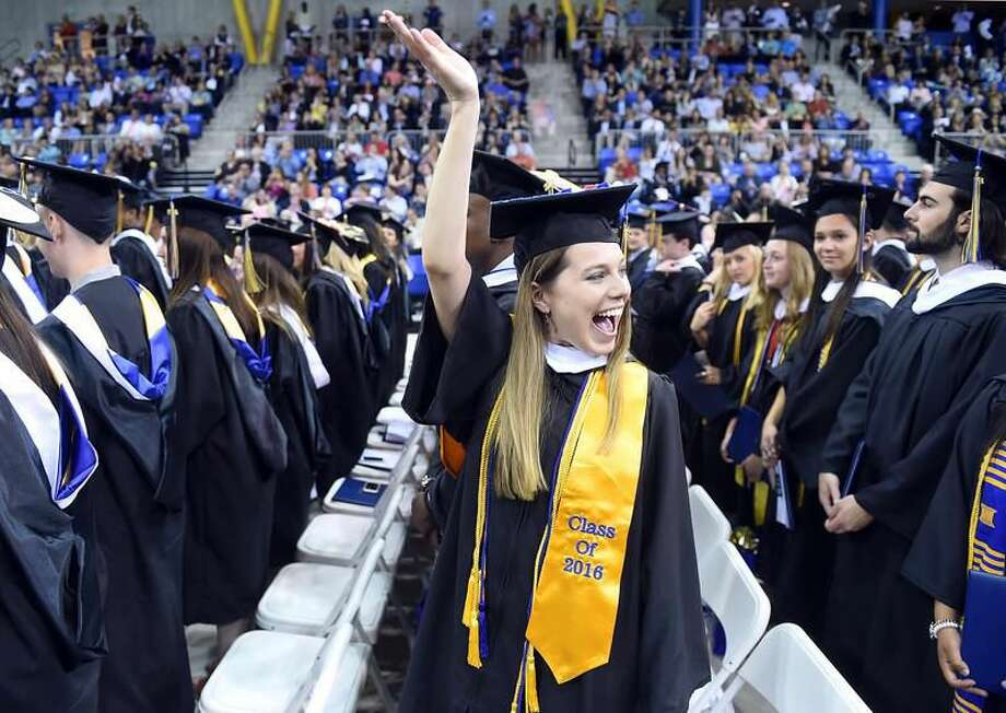 Photo by Arnold Gold/New Haven Register Grace Herman (center) waves to her family during the Quinnipiac University Undergraduate Commencement Saturday morning 5/21/2016.