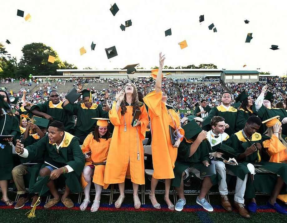 Catherine Avalone/New Haven Register Hamden High School class of 2016 toss their motar boards in the air at the closing of commencement at the Joe Bruno Field.