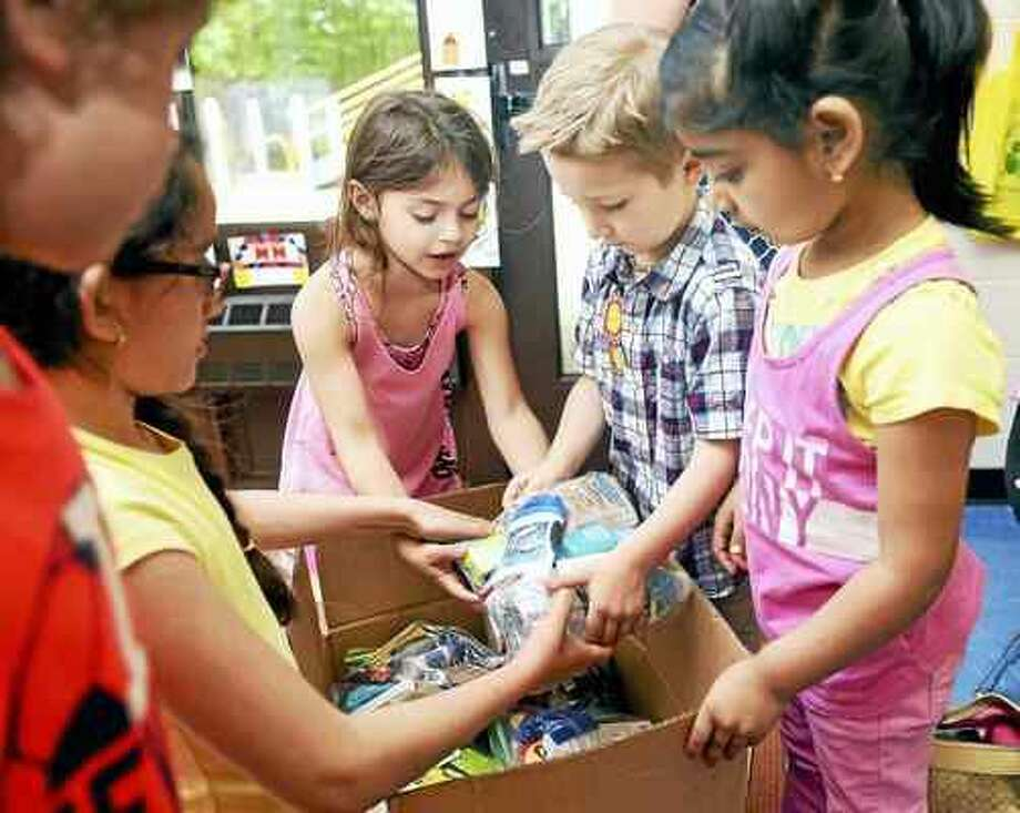 Arnold Gold — New Haven Register Kindergarten classmates help Jeremy Gagne, second from right, load Blessing Bags into boxes at West Woods School in Hamden. The Blessing Bags are for homeless veterans.