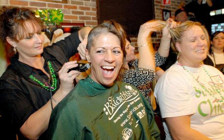 Photos by Peter Hvizdak Hamden firefighter Kimberly Talmadge, right, and Emergency Medical Technician Cody Kelly of American Medical Response, get their heads shaved at the Black Bear Saloon in New Haven for a St. Baldrick fundraiser for children with cancer and Locks of Love. Cutting their hair is Peggy Criscio of Style-N-Go of North Branford, left, and Renne Cullen of JoBella Salon & Spa of New Haven and Branford.