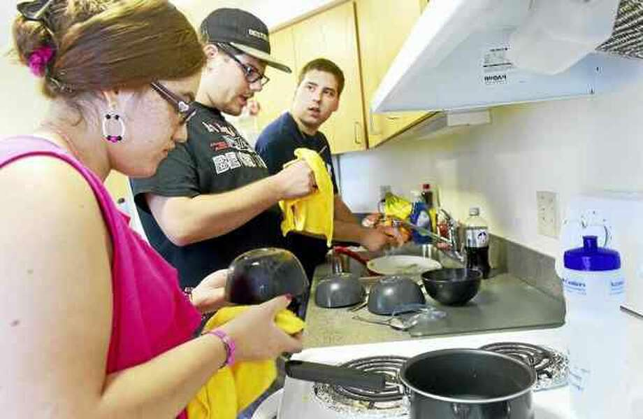 Peter Hvizdak — New Haven Register Julitza Lopez, 19, Jonathan, Meyers, 18, and Brent Bouteiller, 20, wash and dry dishes together in a common area of a dormitory at Quinnipiac University last Tuesday during the Quinnipac University Summer Life Program.