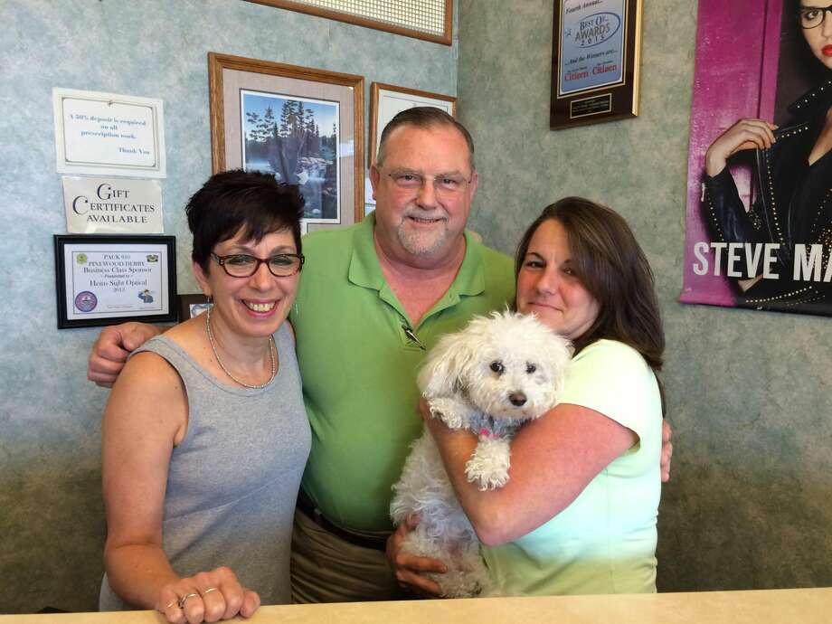 Photo by Lynn Fredricksen Gary Heins, who has owned and operated Heins Sight Optical in the North Haven Shopping Center for 36 years has recently announced his retirement. He is shown here with optician Diane Marshall and office manager Laura Barcsansky who is holding shop mascot Bijou. The store will close officially on August 17, but Heins is encouraging his customers to pick up their glasses prior to August 15.