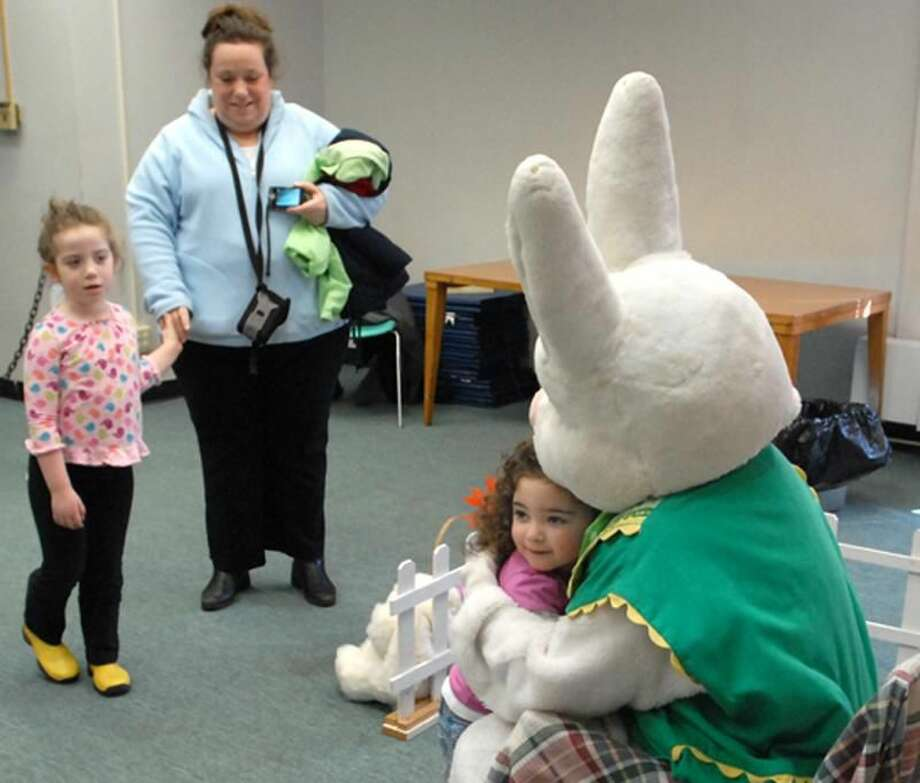 "Photos by Peter Hvizdak Brianna Forslund of Northford, 2, hugs the Easter Bunny after having her photo taken with him during the annual Easter ""Eggstravaganza"" hosted by North Haven's Department of Community Services and Recreation at the Mildred Wakely Recreation Center Saturday."