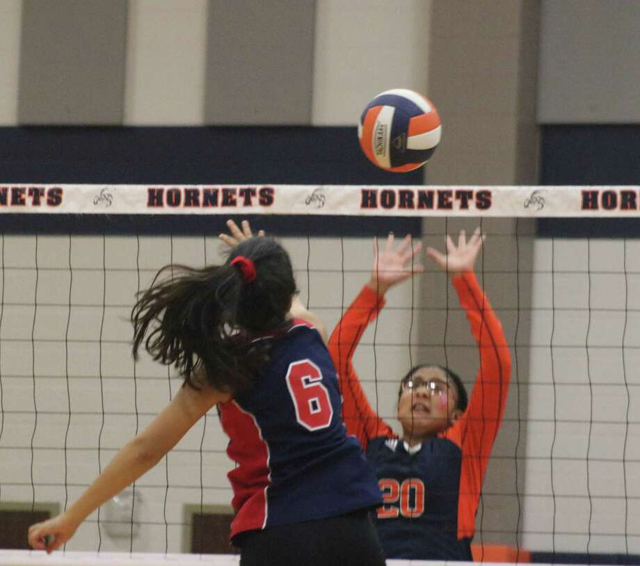 Analece Incenscio attempts to get the ball over the net and over the defense of Gabby Gallegos during Monday night's match. The net proved superior on this play, stopping the ball and giving the Hornets a point. Photo: Robert Avery