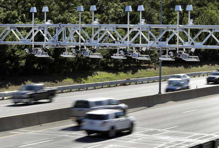 Cars pass under toll sensor gantries hanging over the Massachusetts Turnpike.