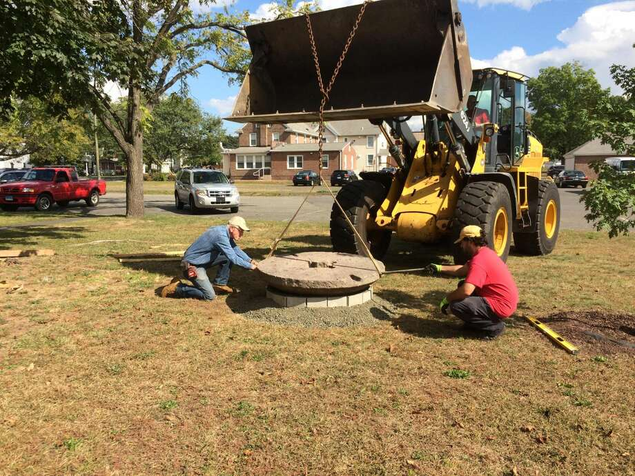 Photo by Lynn Fredricksen Walt Brockett, a member of the North Haven Historical Society and Museums, directs town employees as he positions an old millstone that he has repurposed as a bench. Both the sandstone and the granite millstones have been installed on the lawn between the Cultural Center and the library.