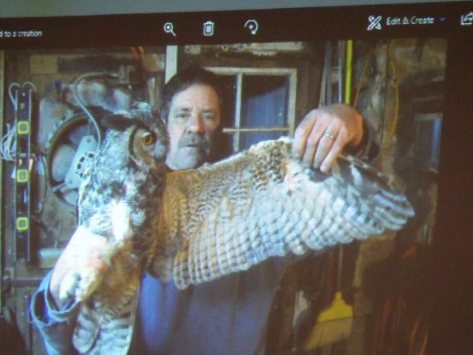 Larry Fischer holding an owl and showing its wing span.