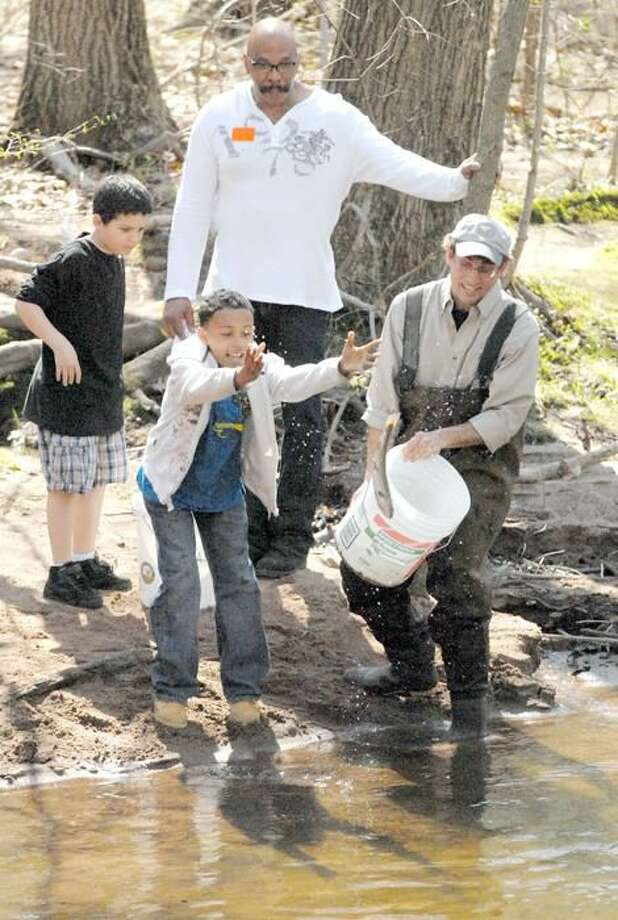 Photo by Joseph Cole Helen St. School fifth-grader Dayjon Bentley tosses one of 400 trout into the Mill River Tuesday, April 6.