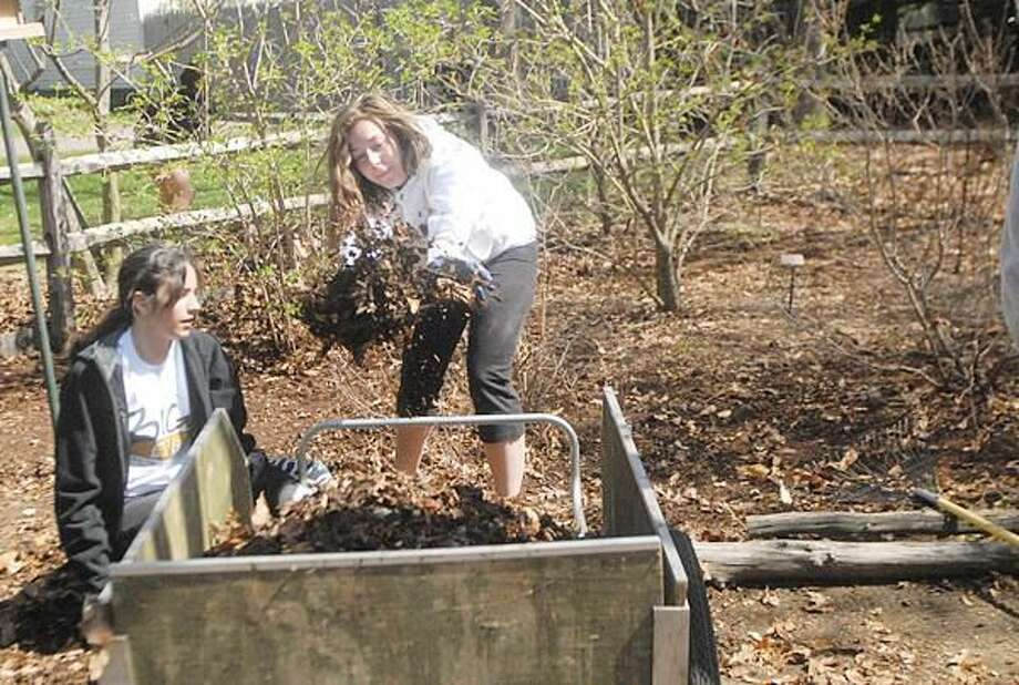 Photo by Joseph Cole Quinnipiac University Freshmen Janelle Argiros (left) and Chelsea Fritzson (right) fill a cart with dried leaves as part of a community service clean-up at Brooksvale Park.