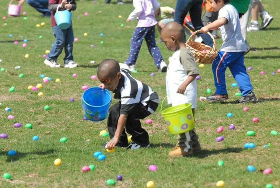 Photo by Joseph Cole Aisalin Washington and Quinton Hebron scramble for brightly-colored eggs spread out acrosss a section of lawn at Town Center Park at Meadowbrook.