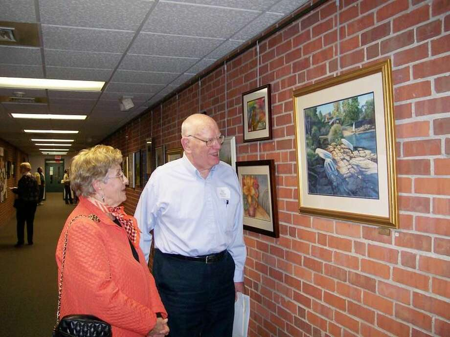 """Photo by Lynn Fredricksen Suggested cutline: Hamden Art League members Ellie Bender and Bob Greiner admire his entry """"Easy Day"""" which won the League's Best in Show Award. Bender was also recognized with the League's Scholfield and Vose Award for her entry, """"Caitlin."""""""