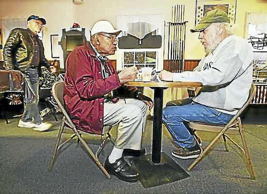 Catherine Avalone — New Haven Register Veterans Charles Patterson, 86, left and Steve Fletcher, 67, both of Hamden, enjoy a free dinner at American Legion Post 88 on Veterans Day, courtesy of local businessman Zafar Farooqui. In the background is Hamden veteran Bob Schwarz, 74.