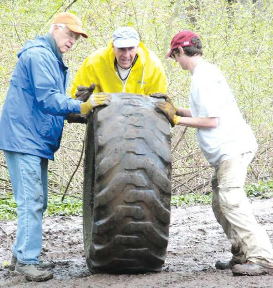 Submitted photo by Melodie Stevens Penton Lonny Gee, John Herpok and Charlie Hoyt (left to right) work to remove one of nearly 30 tires found during a recent cleanup day held by the North Haven Trail Association. Herpok is a member of the NHTA Board of Directors. Hoyt is an Eagle Scout candidate who aims to focus on trail work for his Eagle Scout project.