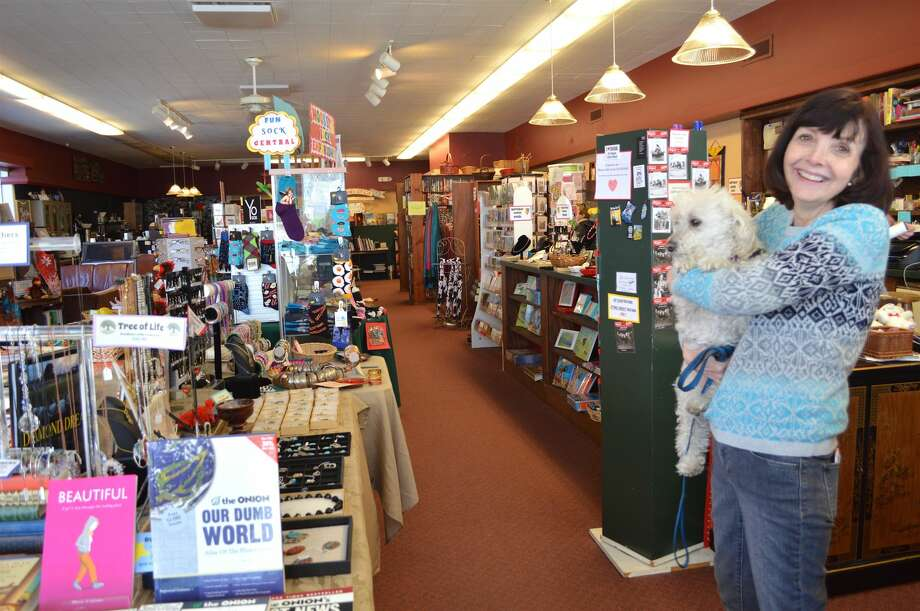 Linda Mooser, owner of Books & Co. on Whitney Avenue these past 23 years, with some jewelry that she created, and her dog, Lily.
