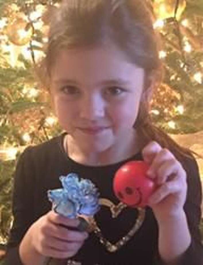 Girl Scout Daisy, Ella Donaldson, shows her unique blue carnation.
