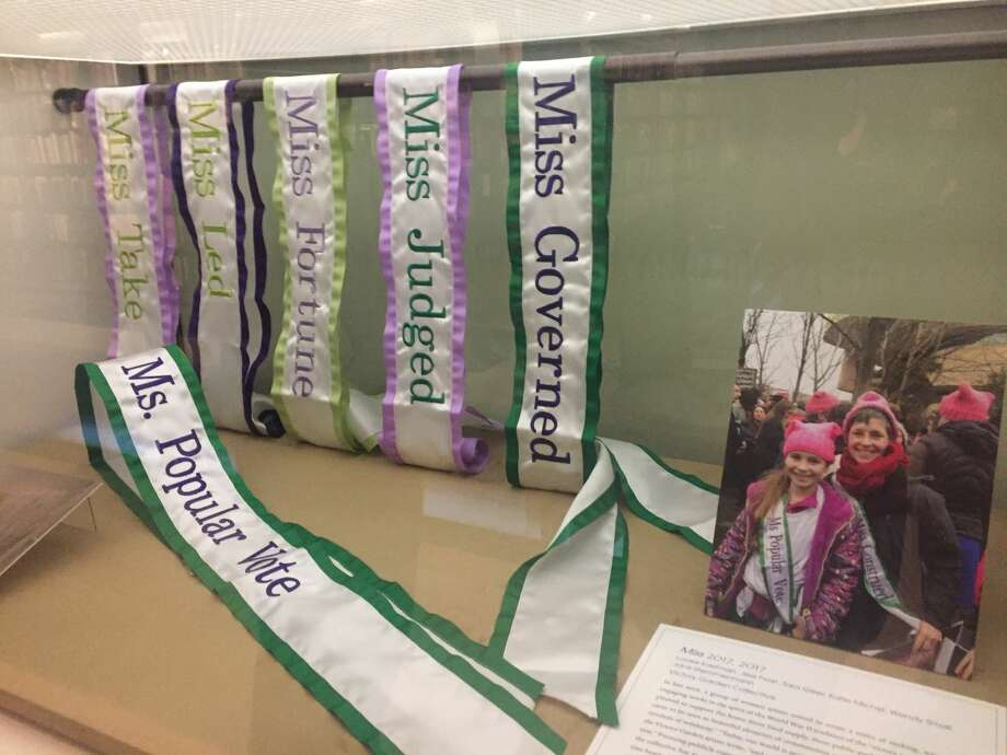 A display case of sashes from the women's rally.