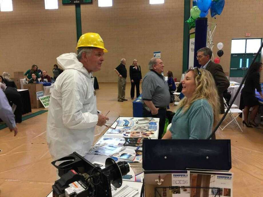 The annual Business & Community Expo organized by the Hamden Regional Chamber of Commerce was held Tuesday at Hamden High School. Above, George DuPont, director of marketing with ServiceMaster Restoration Services, speaks with Paula Ryan of Ryan Oil Company Inc.